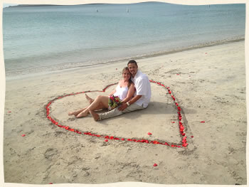 happy couple in rose petal heart on St. Thomas beach